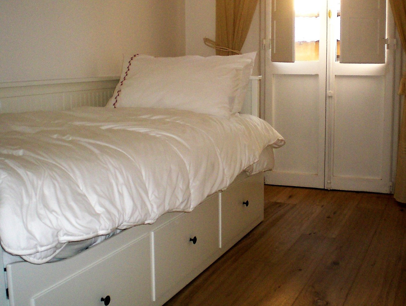 vista interna di una stanza con letto singola e pavimento in legno