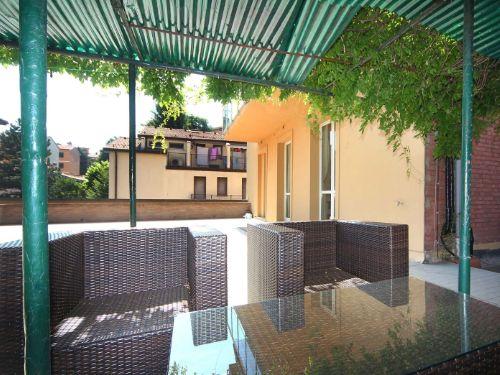 spazio esterno di casa per riposare con divano, poltrona e tavolo