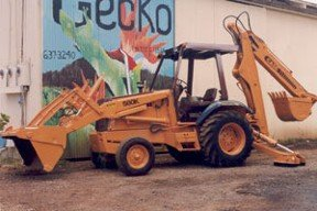 Bulldozer parked in front of Gecko Enterprises painted wall