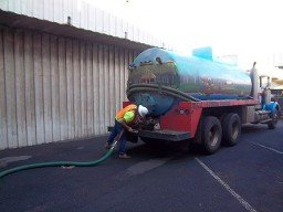 Septic truck with hose going into commercial building