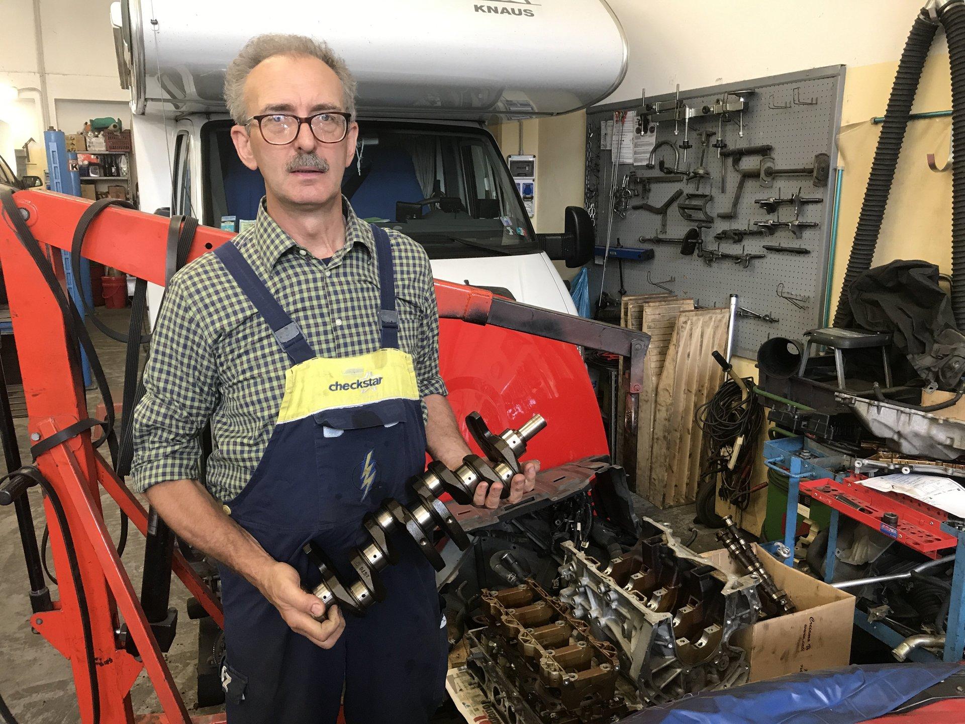 operatore con componente meccanico auto
