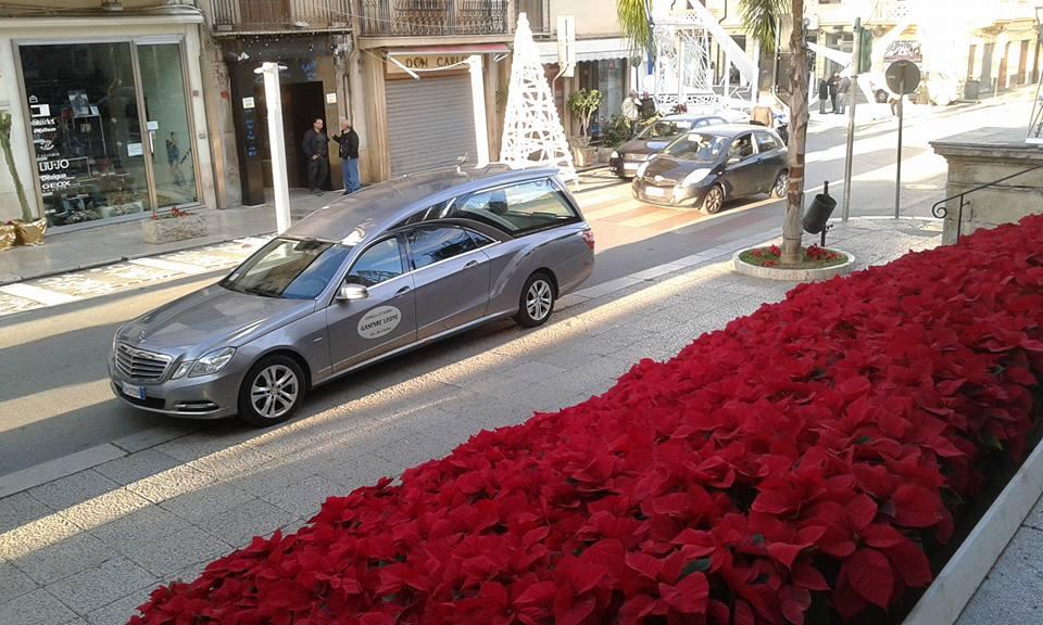 un' aiuola di fiori rossi sulla strada, di fronte il carro funebre parcheggiato e alcune persone sul marciapiede