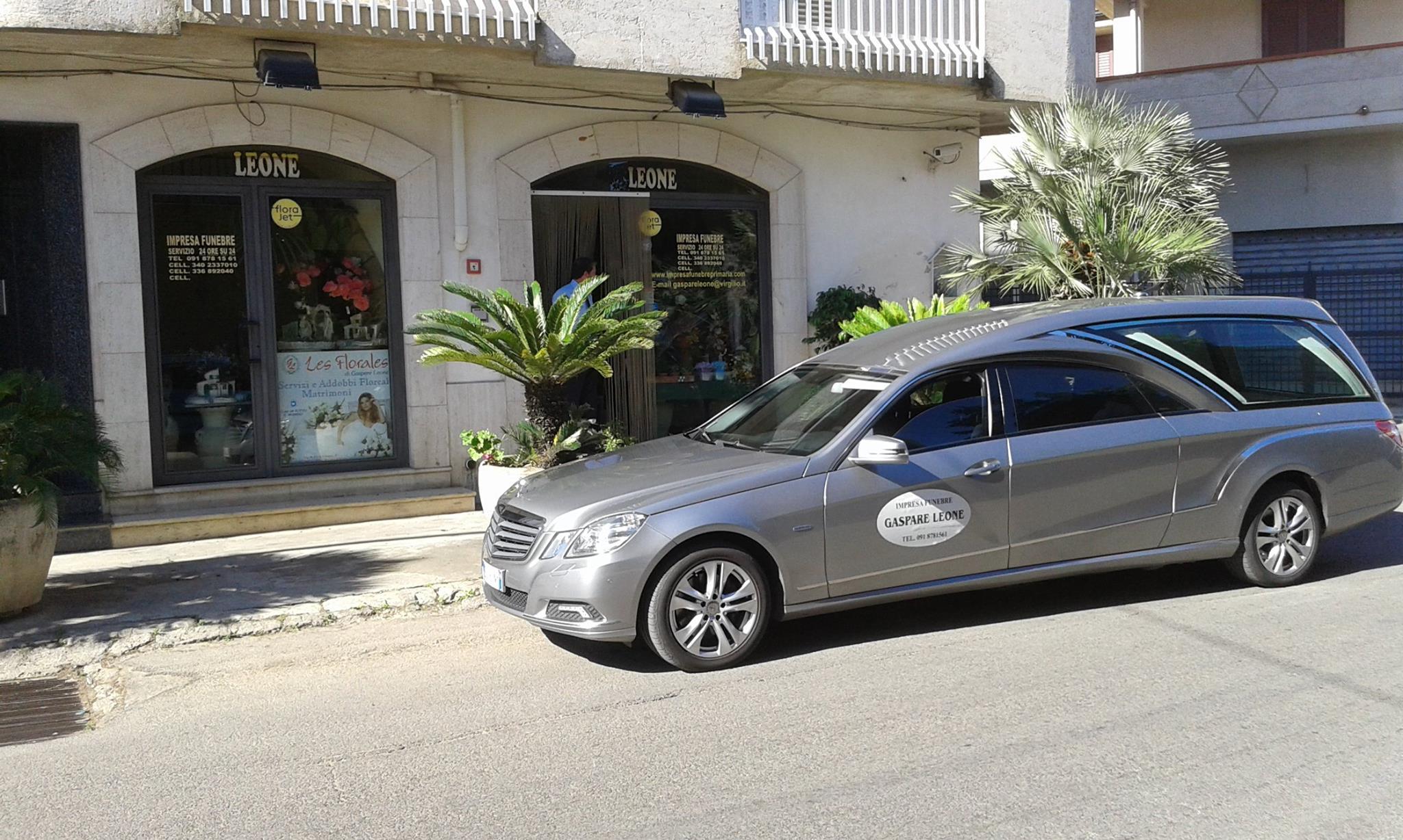 un carro funebre di color grigio visto lateralmente parcheggiato in strada di fronte all'agenzia funebre