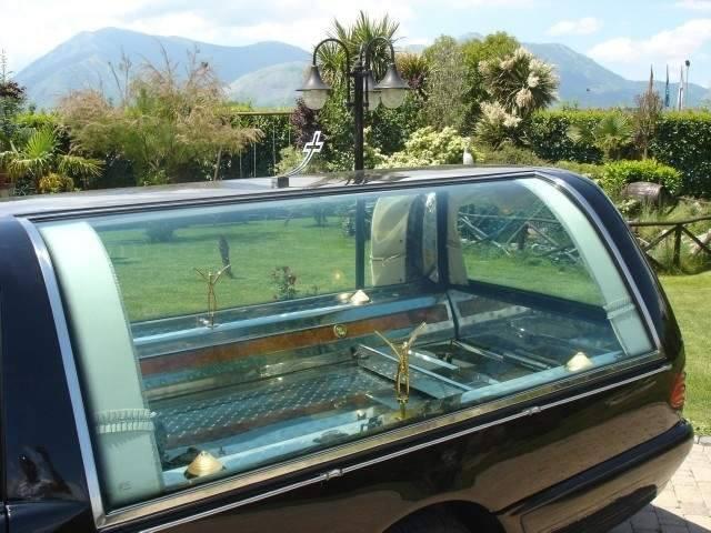 vista laterale attraverso il vetro posteriore del carro funebre della struttura in ferro che ospita la bara