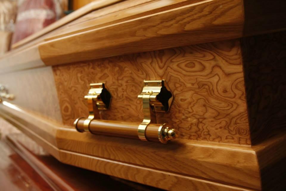 vista ravvicinata della maniglia dorata di una bara in legno chiaro