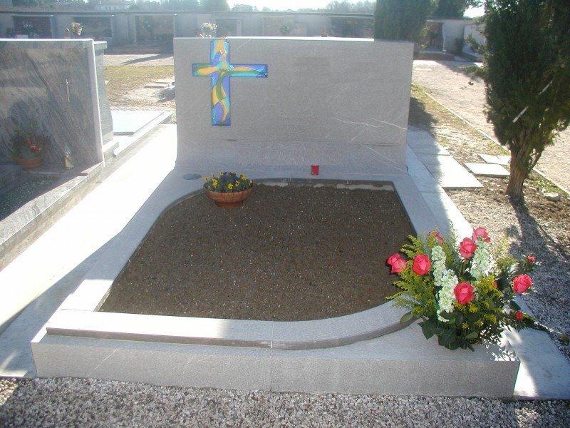 vista di una lapide in  marmo grigio in un cimitero con due vasi di fiori gialli e rosa