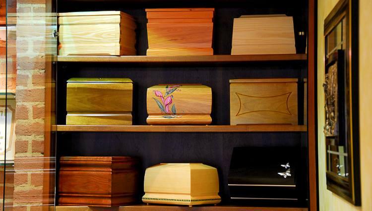 urne delle ceneri in legno lucido di diversi colori esposte all'interno di un armadio su delle mensole