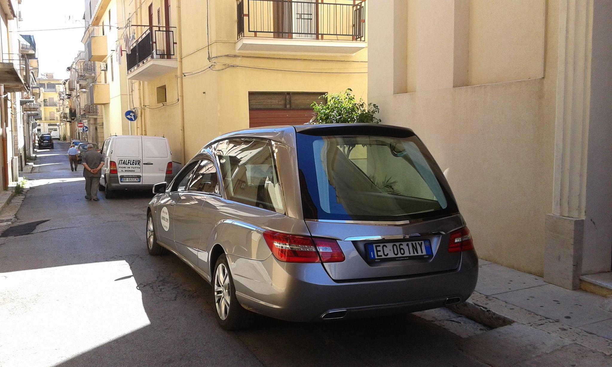 un carro funebre parcheggiato in un vicolo cittadino visto dal dietro