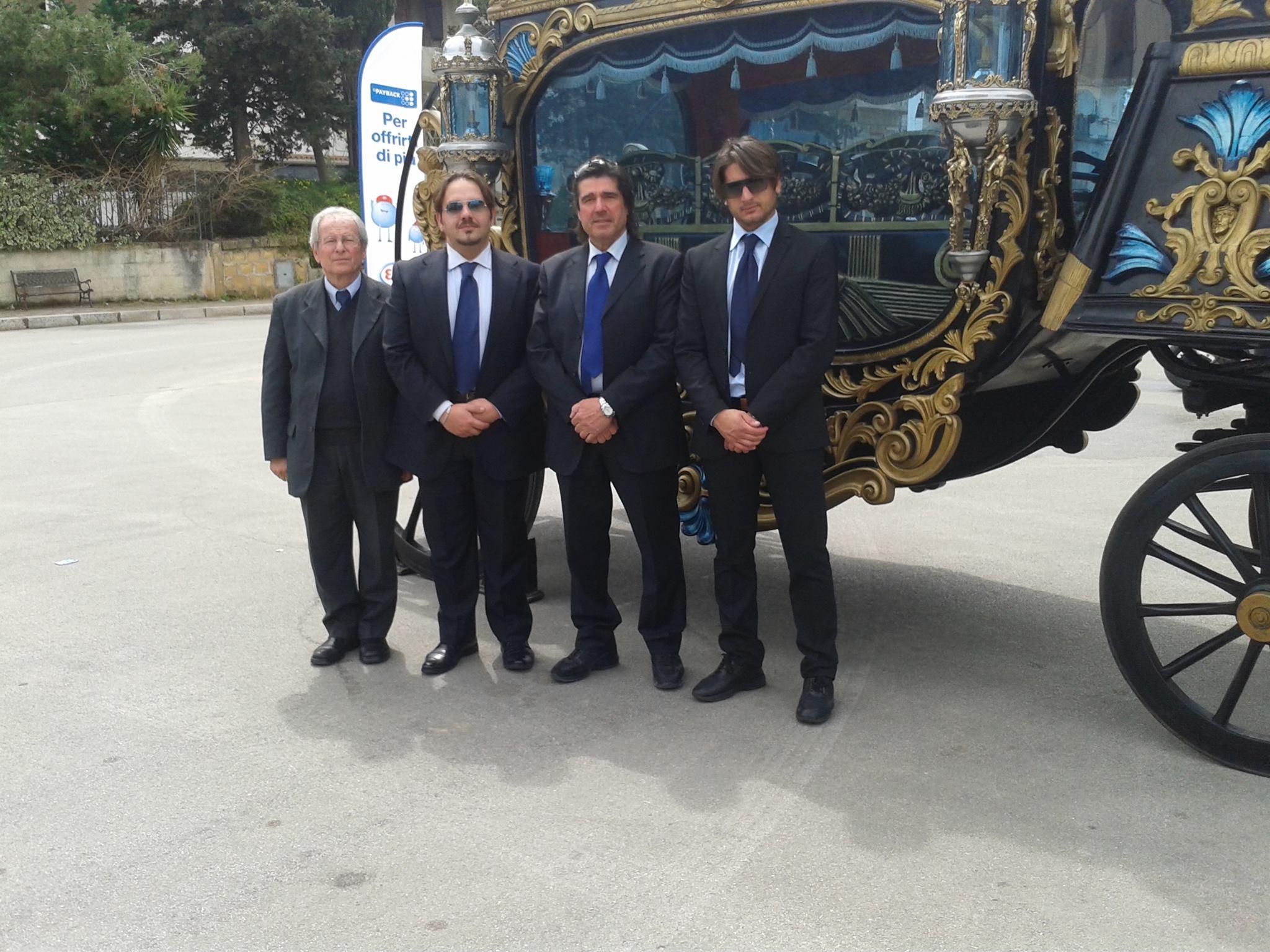 tre uomini in giacca e cravatta di fronte a una carrozza