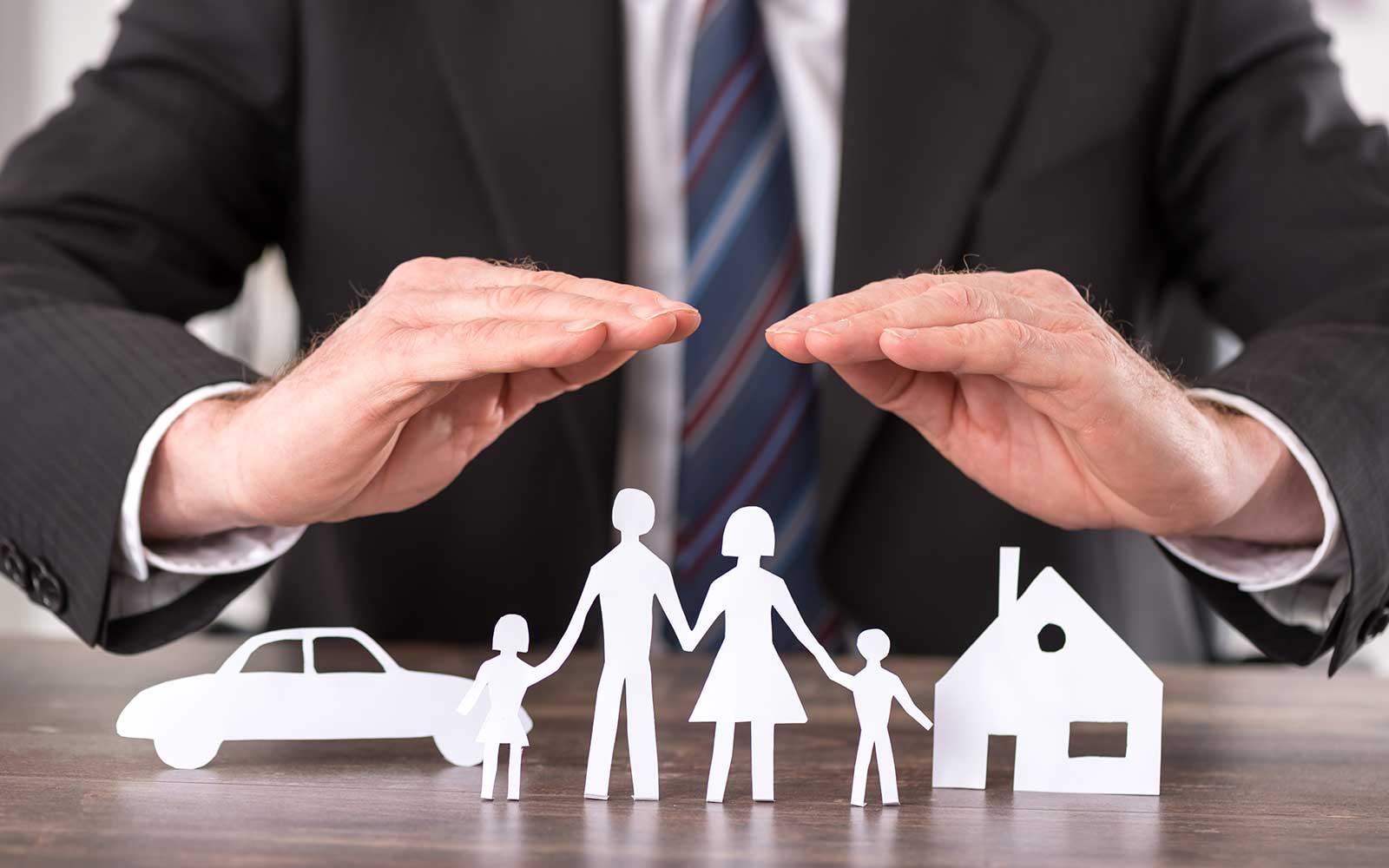 due mani che coprono dei rilievi di cartone di una famiglia, una macchina e una casa