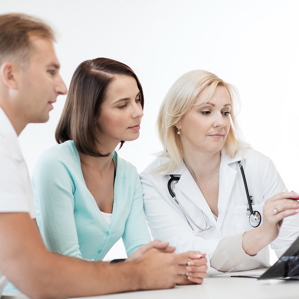 A female doctor explaining a diagnosis to a young woman and her partner