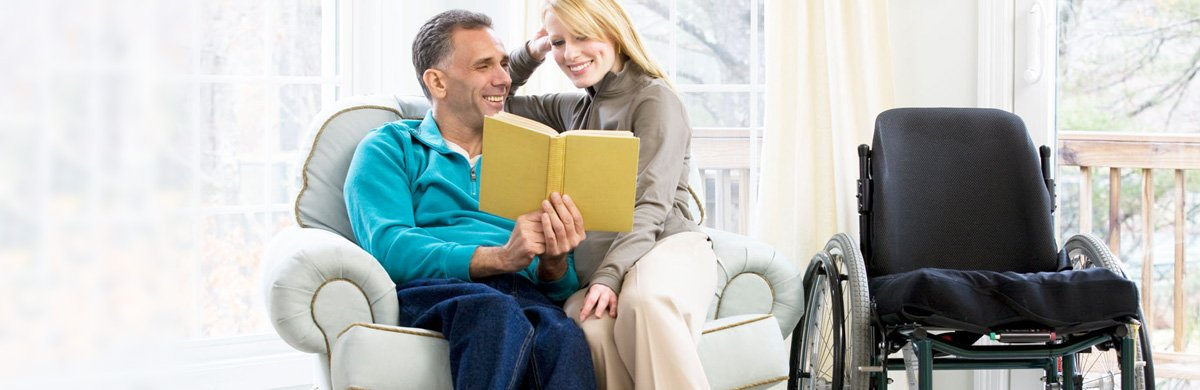 Couple sat in an armchair reading a book (wheelchair next to armchair)
