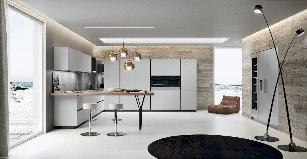 una cucina angolare e delle lampade a sospensione