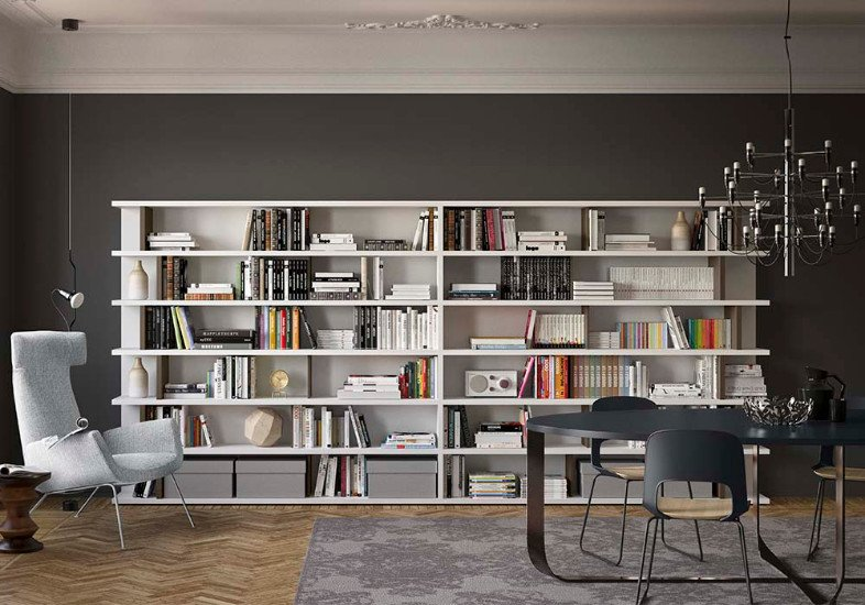 una stanza con dei mobili da libreria intorno di color nero e un divano al centro