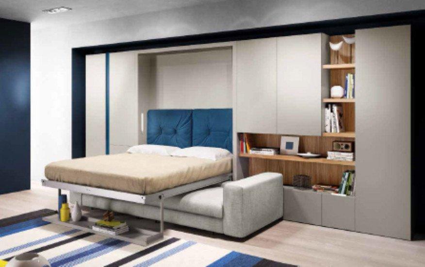 una sala con un divano angolare  di color grigio e un mobile in legno con dei libri