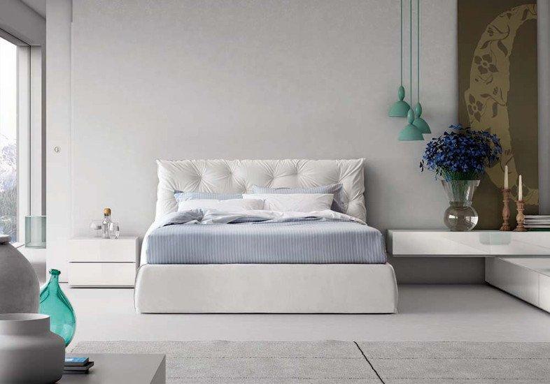 una camera con un letto bianco con la testata imbottita  e dei comodini a muro
