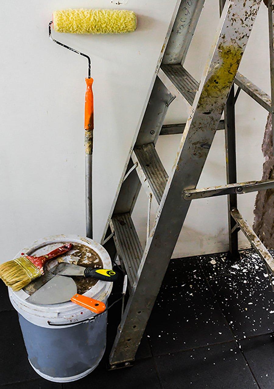 Una scala in alluminio e degli attrezzi da verniciatura