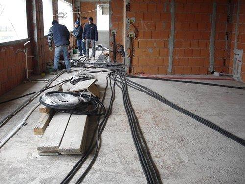 operai mentre installano cavi elettrici in un cantiere