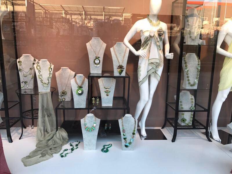 una vetrina con delle collane con perle e pietre di color verde