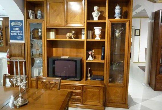 vista frontale di una vetrina in legno con oggetti da casa, televisione, tavolo e sedie