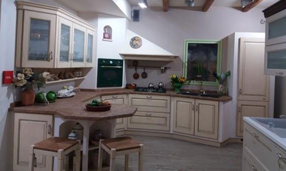 cucina classica in legno con vetrina attaccato su parete, cassetti, tavolo e sedie e arredamento