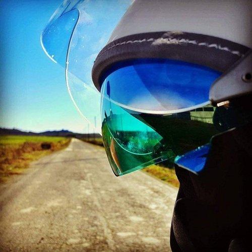 un casco con la visiera e vista di una strada