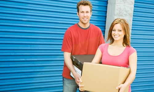 Happy couple holding boxes in front of storage unit