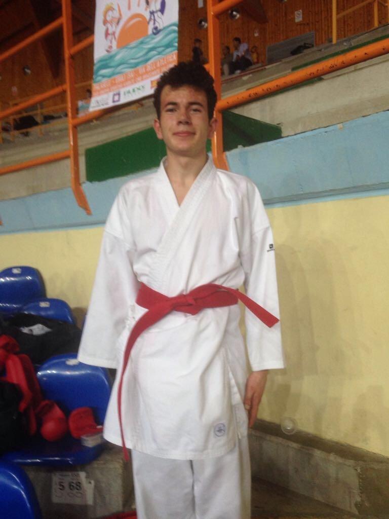 Ragazzo vestito con kimono da karate in cintura rossa