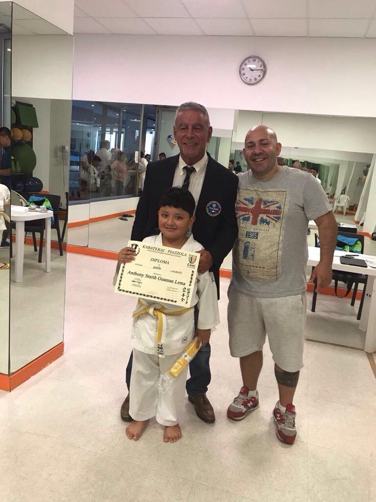 Bambino che ha vinto una targhetta a karate con i suoi maestri
