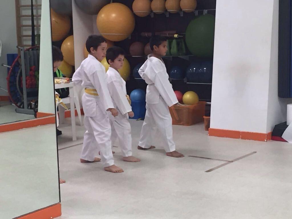 Tre bambini che si allenano a karate