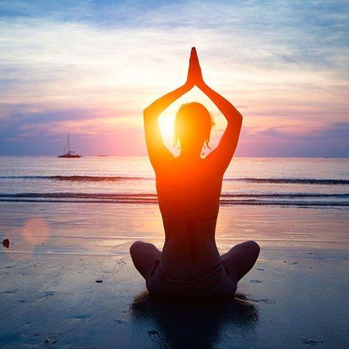 una donna seduta in riva al mare al tramonto in una posizione di yoga
