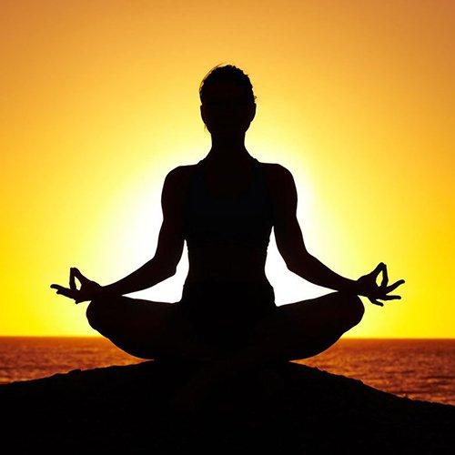 una donna al tramonto in una posizione di yoga