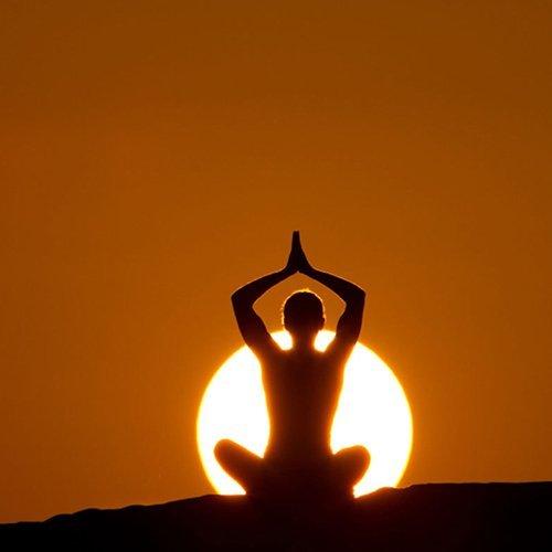 una persona in una posizione di yoga durante il tramonto