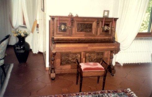 vista interna di una stanza con pianoforte antico, sgabello e arredamento di casa