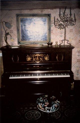 antico pianoforte con parete decorata in una stanza