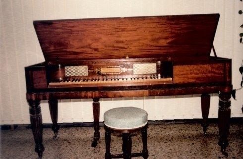 antico pianoforte in una stanza con sgabello e sfondo bianco