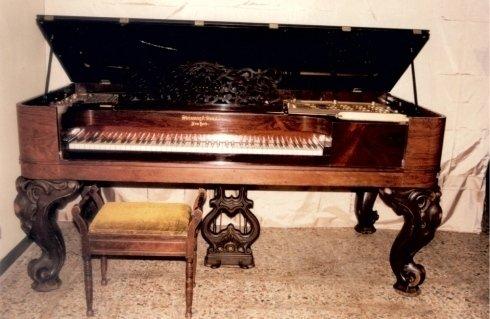 antico pianoforte con sgabello in una stanza