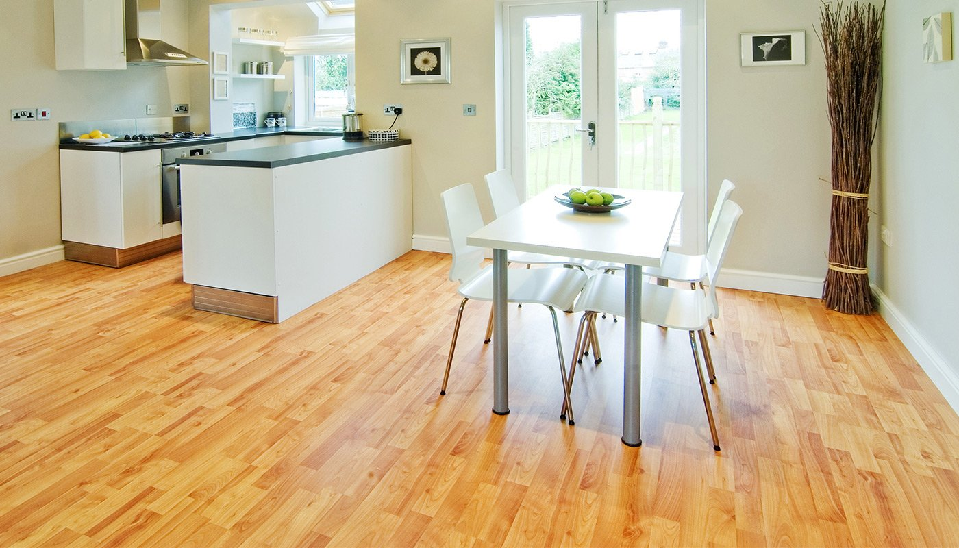 cucina ampia con tavolo con sopra un portafrutta con delle mele verdi,sedie bianche, sulla sinistra cucina con penisola con base in granito