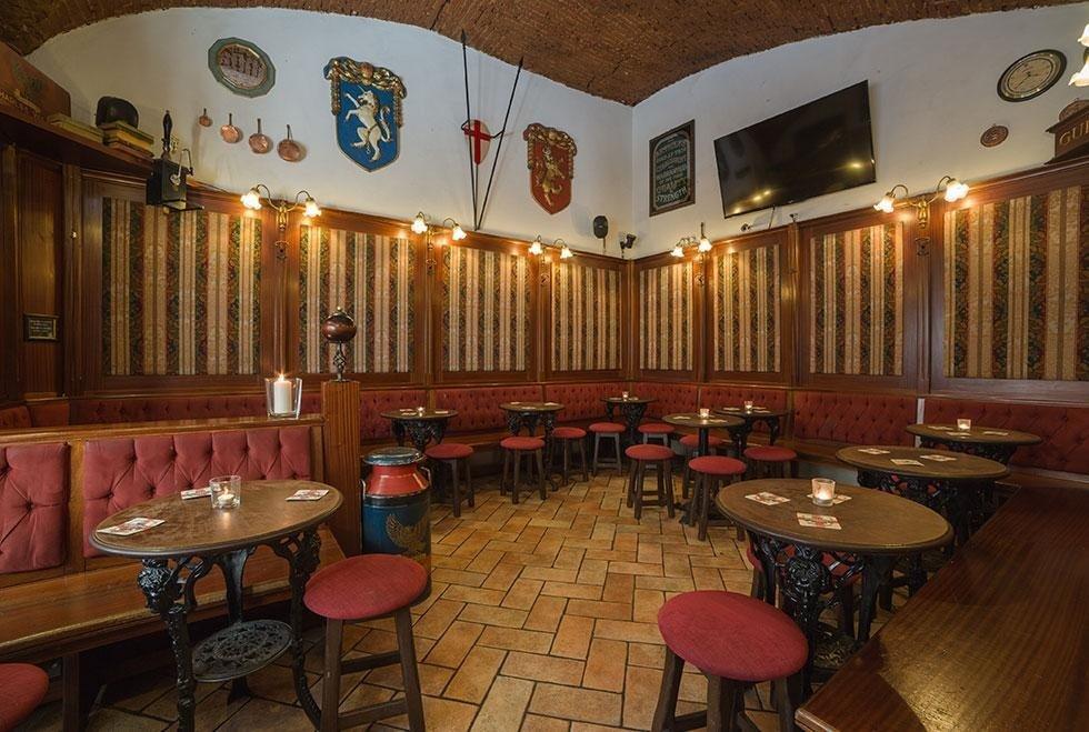 delle panchine con tavoli e sgabelli in un pub