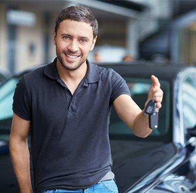 premier automotive man holding car key