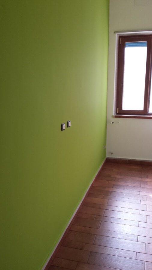 Parete verde in un appartamento con parquet