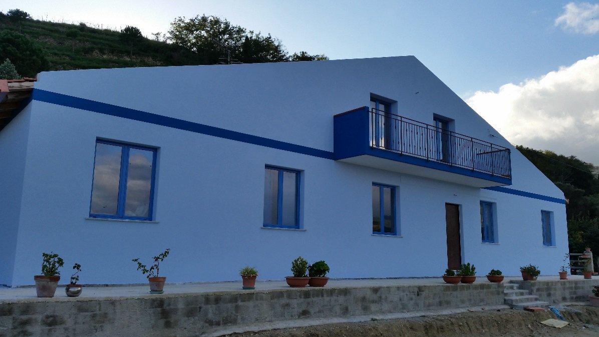casa redipinta in bianco e infissi in blu