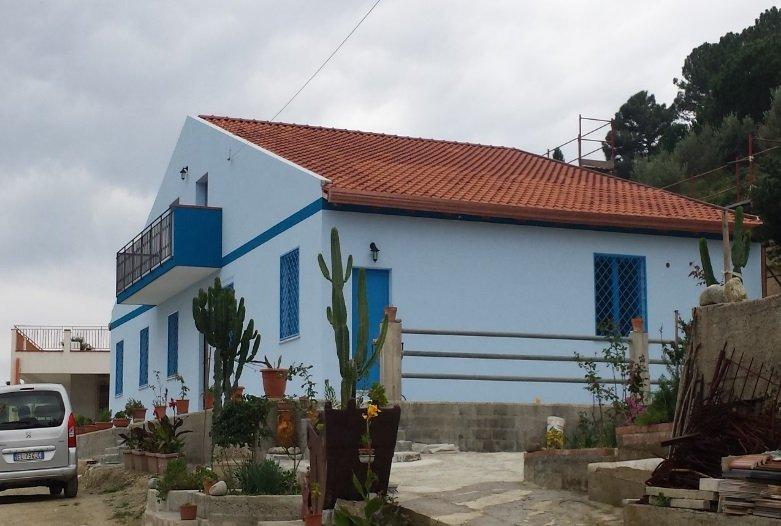 casa ridipinta in bianco e infissi in azzurro