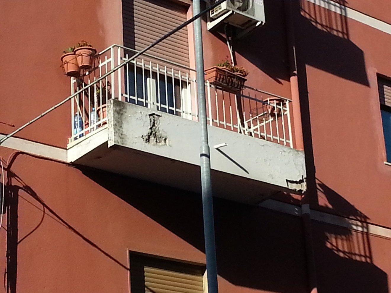 parete rosso marrone con terrazzi bianchi rovinati