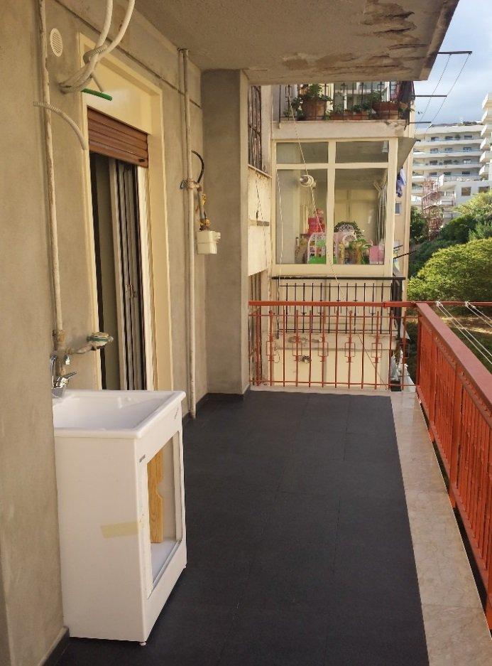 terrazza con pavimento nero, ringhiera arancione e mobiletto con lavandino