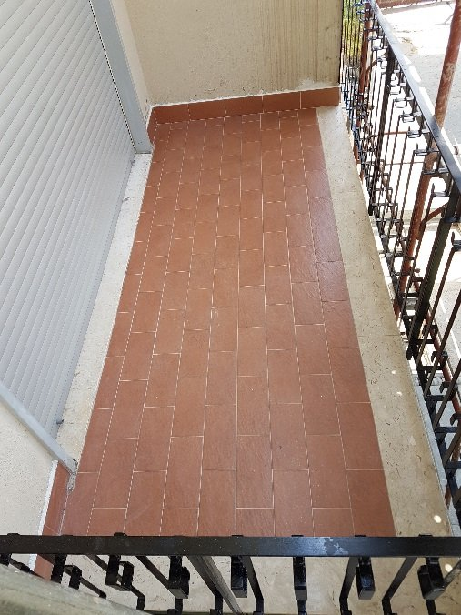 terrazzo con piastrelle marroni e ringhiera in ferro