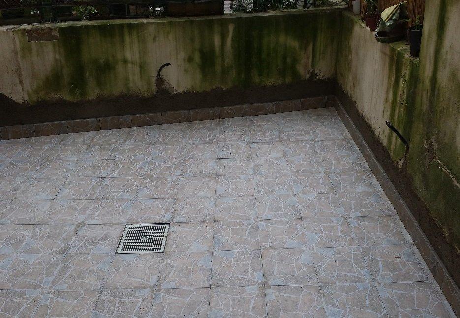 pavimento con piastrelle effetto pietra con grata di scolo
