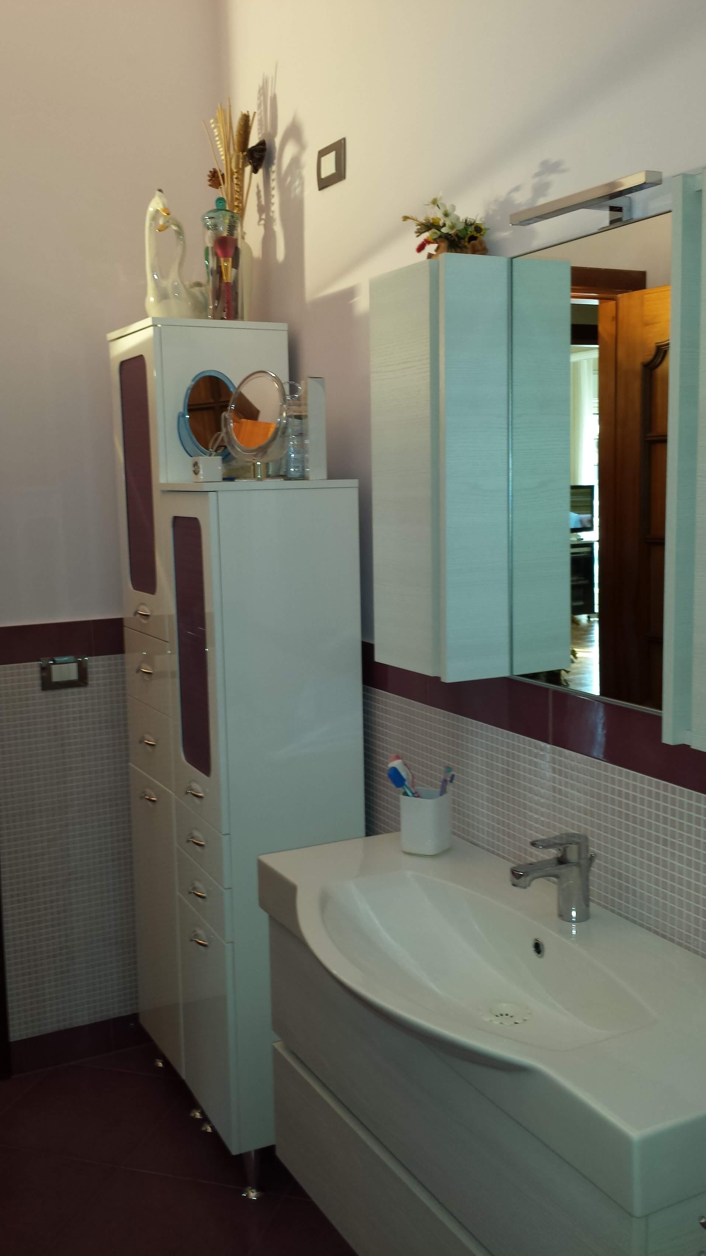 bagno con mobili chiari e dettagli in porpora per riprendere il muro a mosaico