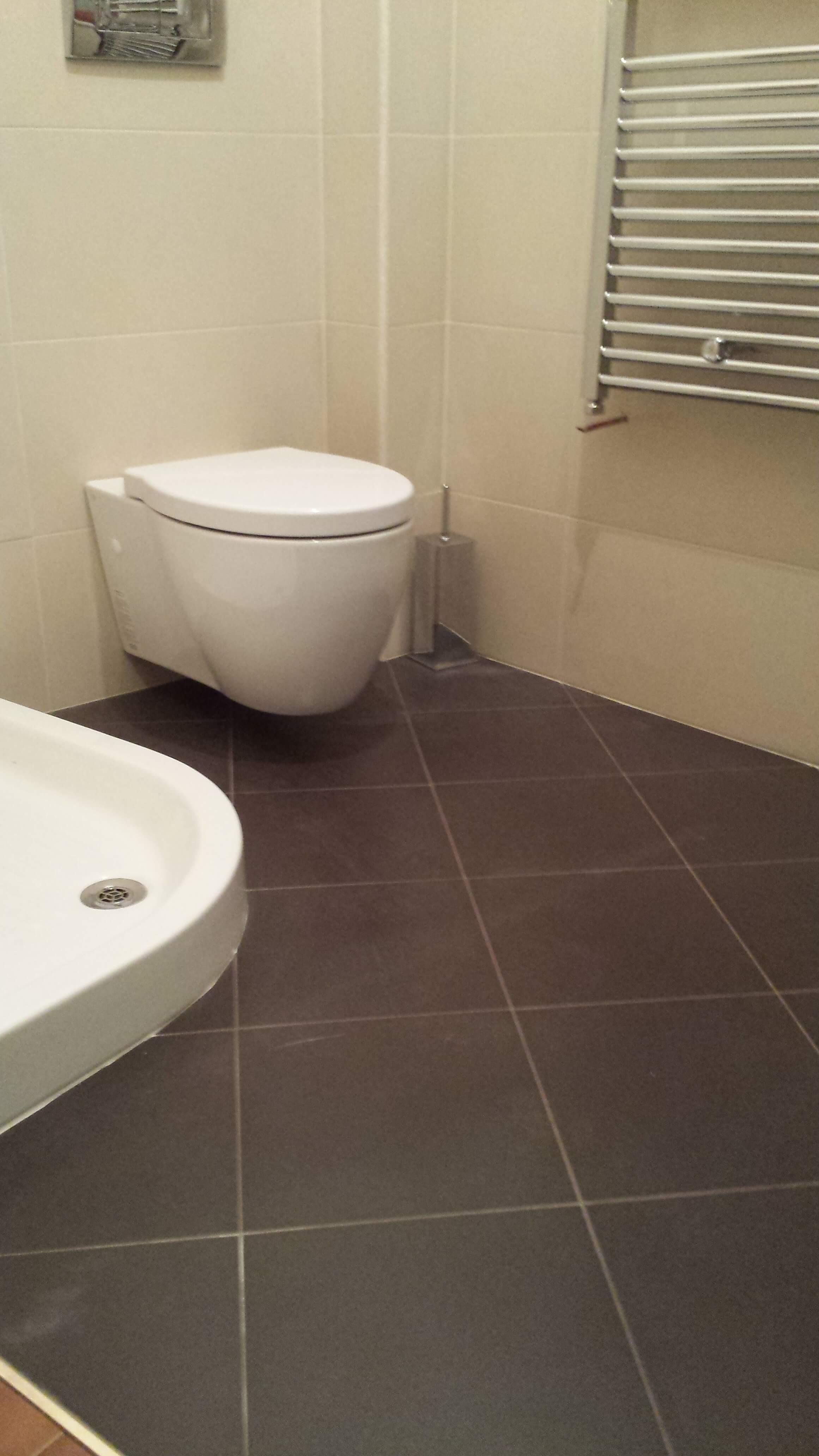 bagno con pavimento con piastrelle scure, bidé bianco e scaldasalviette