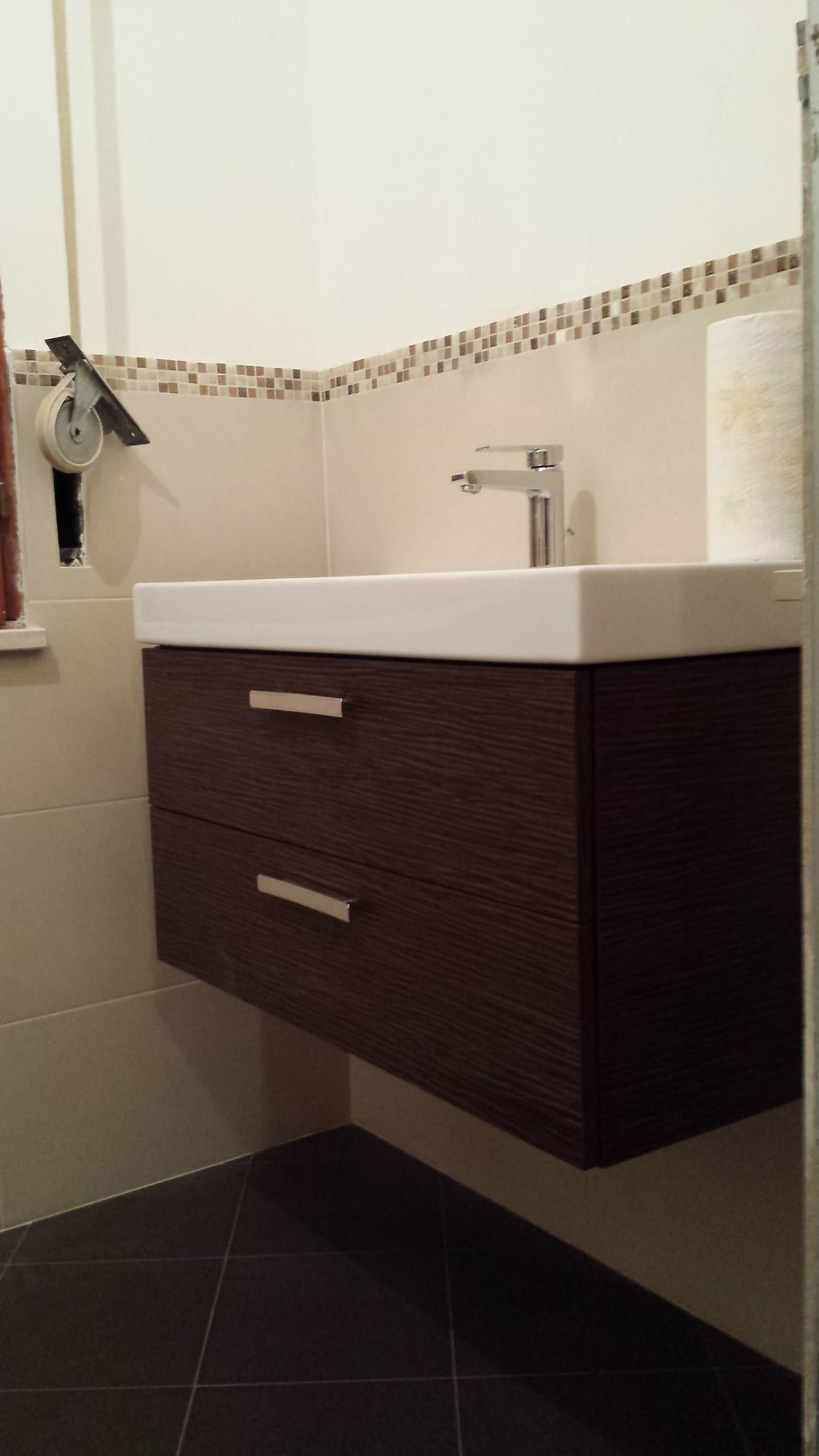 lavandino bianco incastonato in un mobile in legno scuro e muro piastrellato chiaro